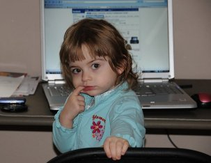 Toddler sitting in front of laptop © Tammra McCauley