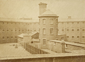 Old photo of Millbank Prison in the 1880s showing an exercise yard and a tower